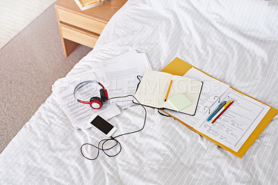 Buy stock photo Shot of a notebook, documents and a cellphone with headphones lying on a bed