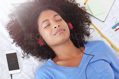 Buy stock photo Shot of a young woman listening to music while lying on her bed