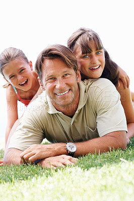 Buy stock photo Portrait of man lying on grass with his daughters and smiling