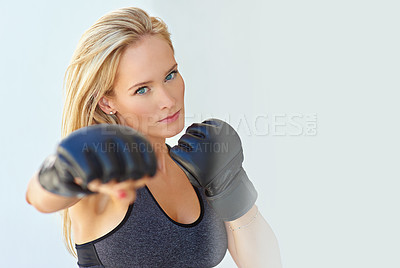 Buy stock photo Shot of a sporty young woman training with mma gloves