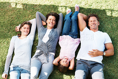 Buy stock photo Top view of family lying together on grass and relaxing