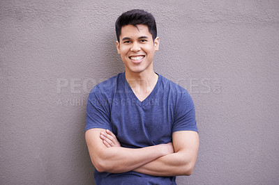 Buy stock photo Portrait of a young man standing against a gray wall