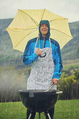 Buy stock photo Shot of a man happily barbecuing in the rain