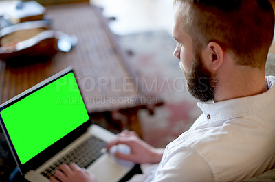 Buy stock photo Shot of a young man using a laptop with a green screen at home