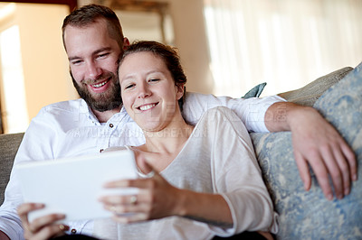 Buy stock photo Shot of a young couple relaxing at home on the sofa with a digital tablet