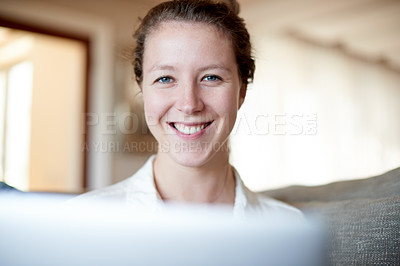 Buy stock photo Cropped portrait of a young woman using her laptop while sitting on the sofa at home