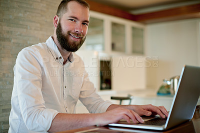 Buy stock photo Shot of a young man working on a laptop at home