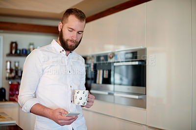 Buy stock photo Shot of a young man using his mobile phone at home
