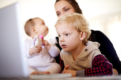 Buy stock photo Shot of a young family sitting with a laptop at home