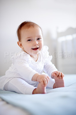 Buy stock photo Shot of an adorable baby girl sitting on a bed