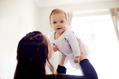 Buy stock photo Shot of a young mother holding her baby daughter