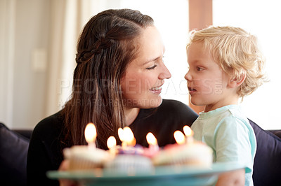Buy stock photo Shot of a little boy and his mother celebrating his birthday with cupcakes