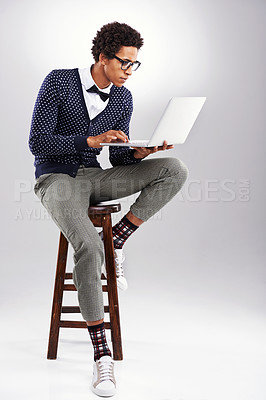Buy stock photo Studio shot of a young man using a laptop against a gray background