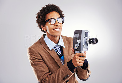 Buy stock photo Shot of a young man holding a video camera against a gray background