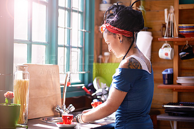 Buy stock photo Shot of a young woman with dreadlocks washing dishes in the kitchen