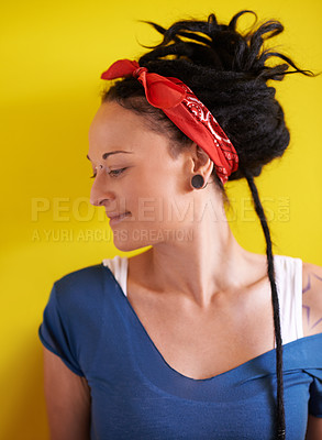 Buy stock photo Shot of an attractive woman with dreadlocks standing against a yellow background