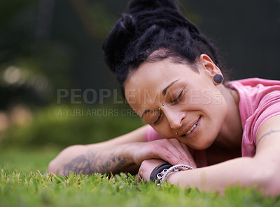 Buy stock photo Shot of a woman with dreadlocks lying on the grass with her eyes shut