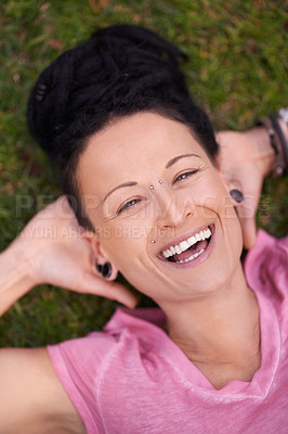 Buy stock photo High angle shot of a woman lying on the grass