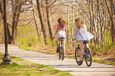 Buy stock photo Rearview shot of two friends out for a bike ride in a park
