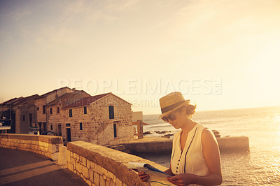 Buy stock photo Shot of a young woman reading a map while out traveling
