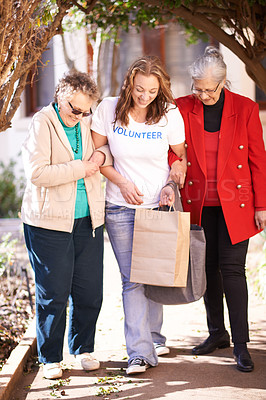 Buy stock photo Shot of a volunteer worker taking two senior women shopping