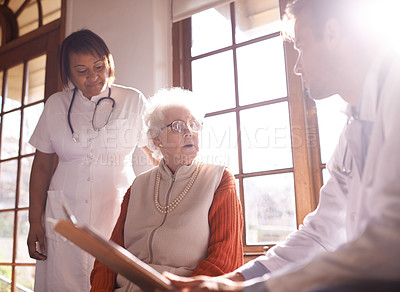 Buy stock photo Shot of a doctor and nurse working with a senior woman in a retirement home