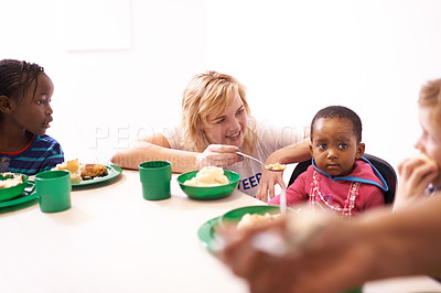 Buy stock photo Cropped shot of a volunteer workers feeding a child during lunch