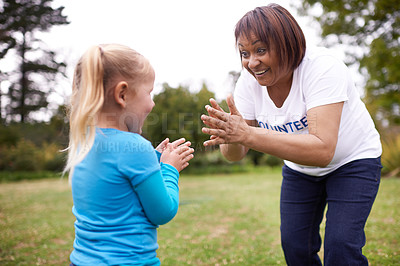 Buy stock photo Shot of a volunteer worker playing with a child outdoors