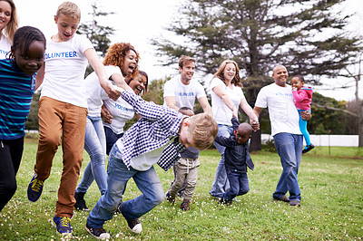 Buy stock photo Shot of a volunteer workers playing with children outdoors
