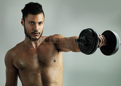 Buy stock photo Studio shot of a young man working out with a dumbbell against a gray background