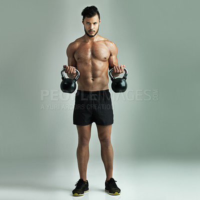 Buy stock photo Studio shot of a young man working out with kettle bells against a gray background