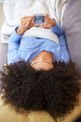 Buy stock photo High angle shot of a young woman using her cellphone while relaxing on the sofa