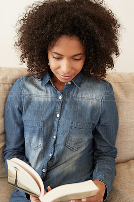 Buy stock photo Shot of a young woman reading a book on the sofa at home