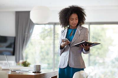 Buy stock photo Shot of a young businesswoman looking at a notebook in an office