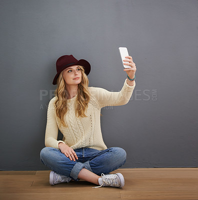Buy stock photo Shot of a young woman using her cellphone while sitting against a gray background