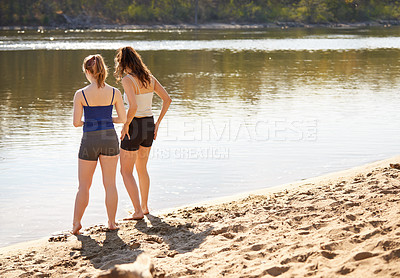 Buy stock photo Shot of two young women standing by a lake