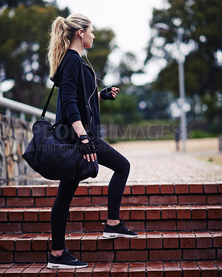 Buy stock photo Shot of a sporty young woman carrying a gym bag