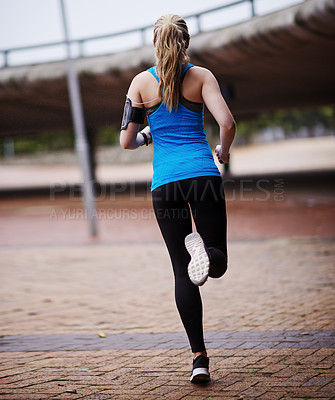 Buy stock photo Rearview shot of a young woman out running
