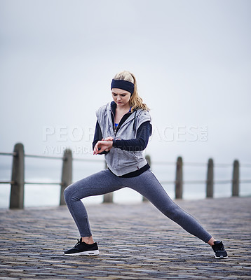 Buy stock photo Shot of a young woman checking her watch while exercising outdoors