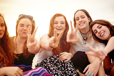 Buy stock photo Shot of a group of girlfriends showing peace gestures outdoors
