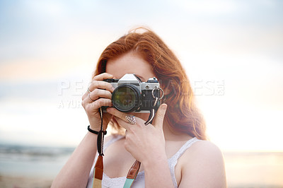 Buy stock photo Shot of a young photographer taking pictures with her camera outdoors