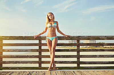 Buy stock photo Shot of a young woman in a bikini on a walkway near the beach