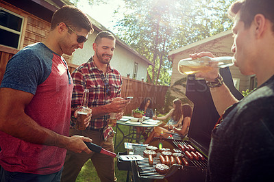 Buy stock photo Shot of a group of friends having a barbecue outside