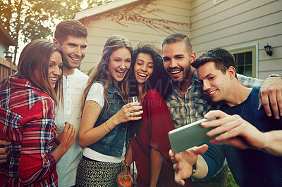 Buy stock photo Shot of a group of friends taking a selfie outside