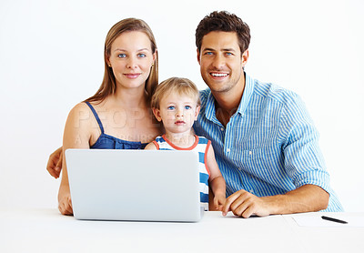 Buy stock photo Portrait of family of three sitting together at a table using laptop and smiling
