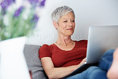 Buy stock photo Shot of a mature woman sitting in her living room using a laptop