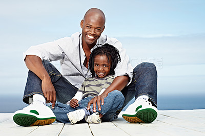 Buy stock photo Portrait of a smiling father and son sitting outside