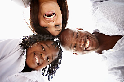 Buy stock photo Low angle portrait of a young family standing in a huddle outside