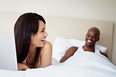 Buy stock photo Shot of a young woman using a laptop while lying in bed with her husband