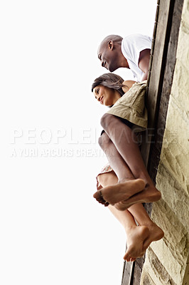 Buy stock photo Low angle shot of a young couple sitting on the edge of a boardwalk